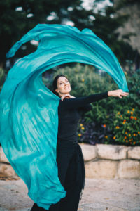 Lurainya of Moon Gypsy Productions bellydancing in black fringe with teal silk veil swirling overhead