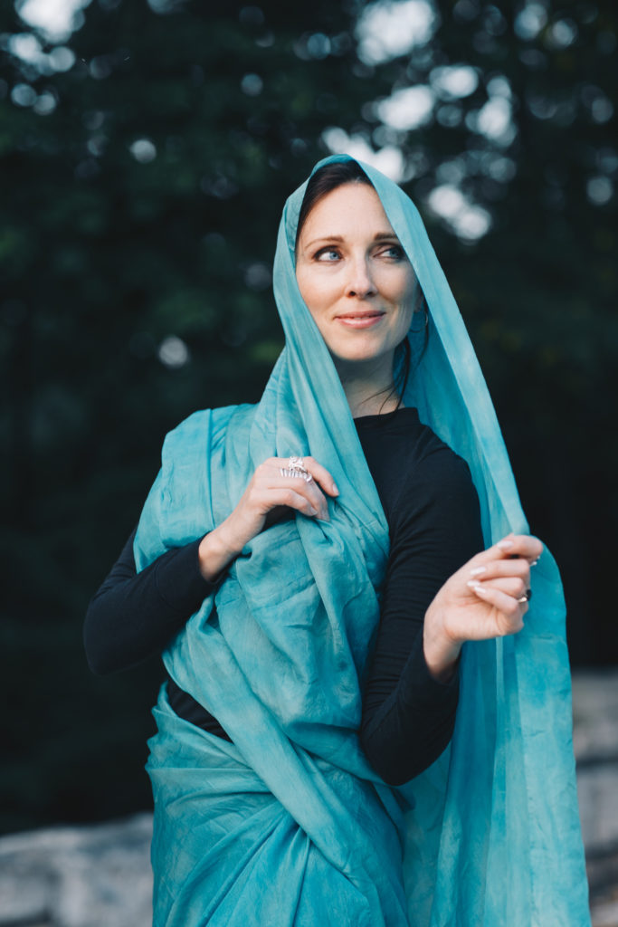 Lurainya Koerber of Moon Gypsy Productions smiling and posing with teal silk veil