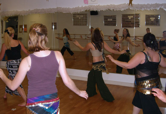 Lurainya Koerber of Moon Gypsy Productions teaching belly dance moves to students wearing coin scarves during class in Hatboro, PA