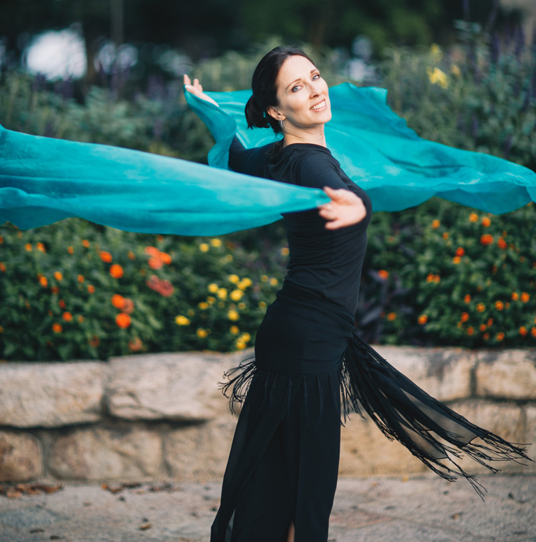 Lurainya Koerber of Moon Gypsy Productions belly dance demo outdoors spinning with teal silk veil