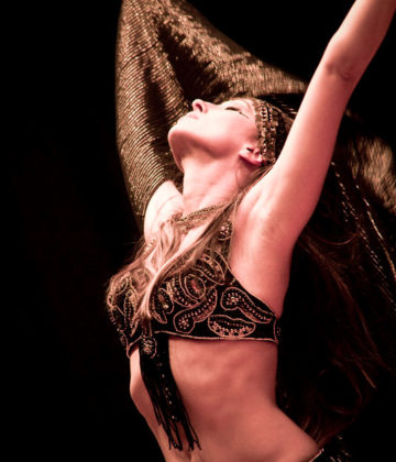 Lurainya Koerber of MoonGypsy Productions on stage performing belly dance, wearing black and gold two-piece cabaret costume with black veil