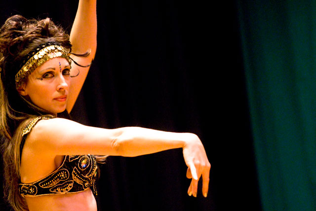 Lurainya Koerber of MoonGypsy Productions, performing modern bellydance in black and gold cabaret costume
