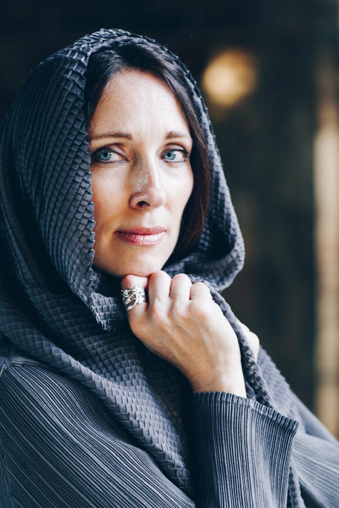Lurainya Koerber modeling headshot photo showing blue eyes behind draping scarf wearing custom jewelry