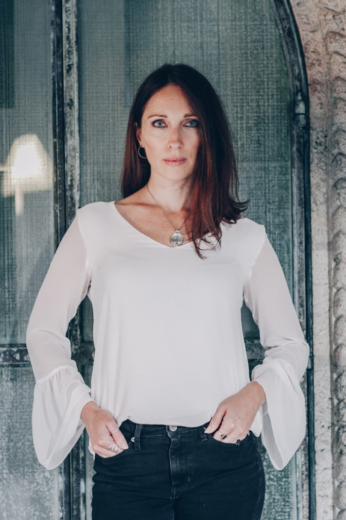 Lurainya Koerber modeling portrait white blouse with black jeans and custom necklace