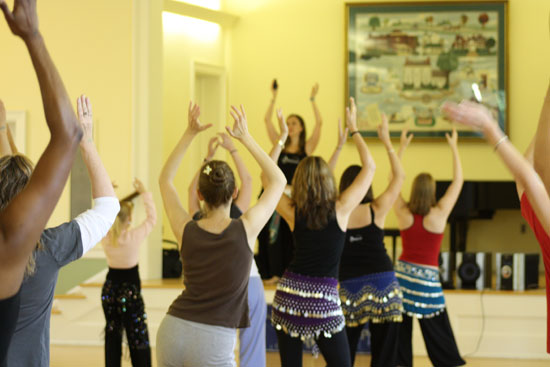 Lurainya Koerber of Moon Gypsy Productions teaching belly dance workshop, students wearing coin scarves