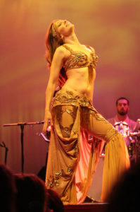 Lurainya Koerber of Moon gypsy Productions performing bellydance on stage in camel color two-piece cabaret costume at World Cafe Live with Animus
