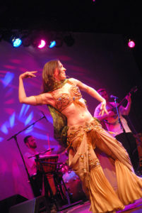 Lurainya Koerber performing belly dance in cabaret costume with green silk veil to live music with Bill Koutsouros of Animus at World Cafe Live in Philadelphia, PA