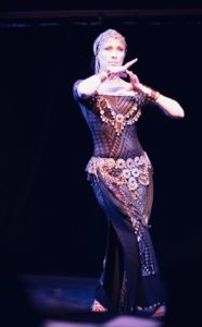 Lurainya Koerber from MoonGypsy Productions striking a bellydance pose mid performance at the Bucks Fever Talent Show
