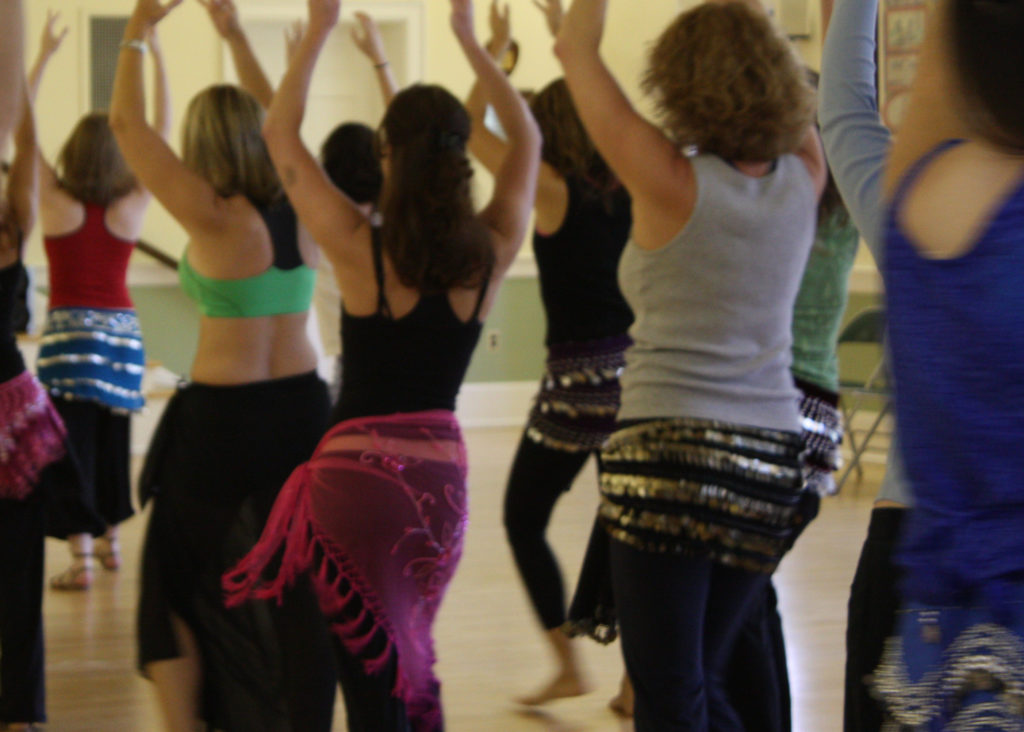 Lurainya teaching bellydance class to women of all ages and ethnicities in coin scarves.